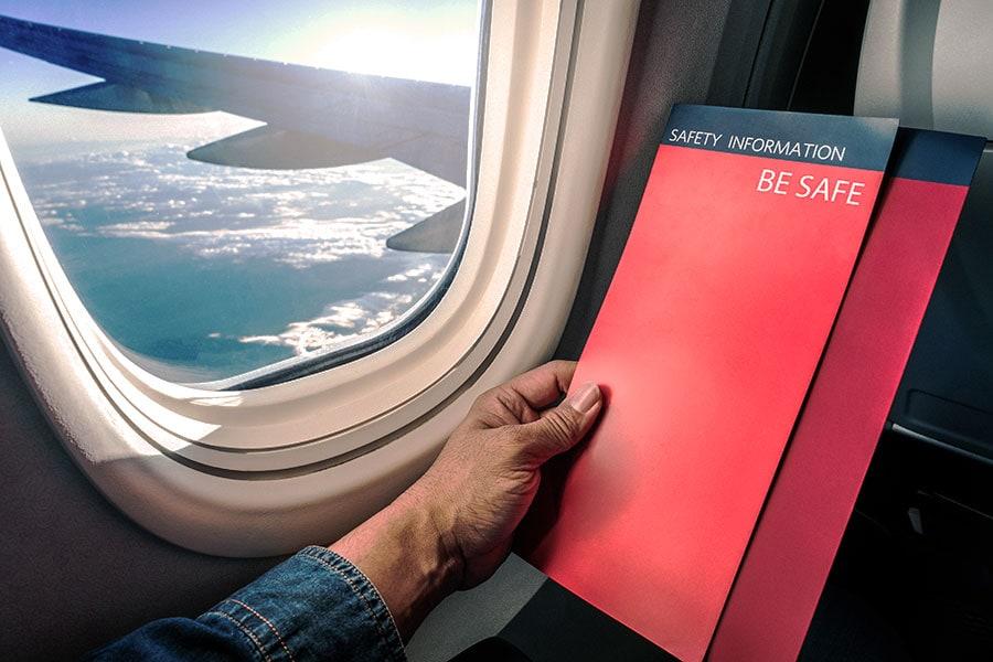 Pasajero mirando las instrucciones de seguridad en el avión