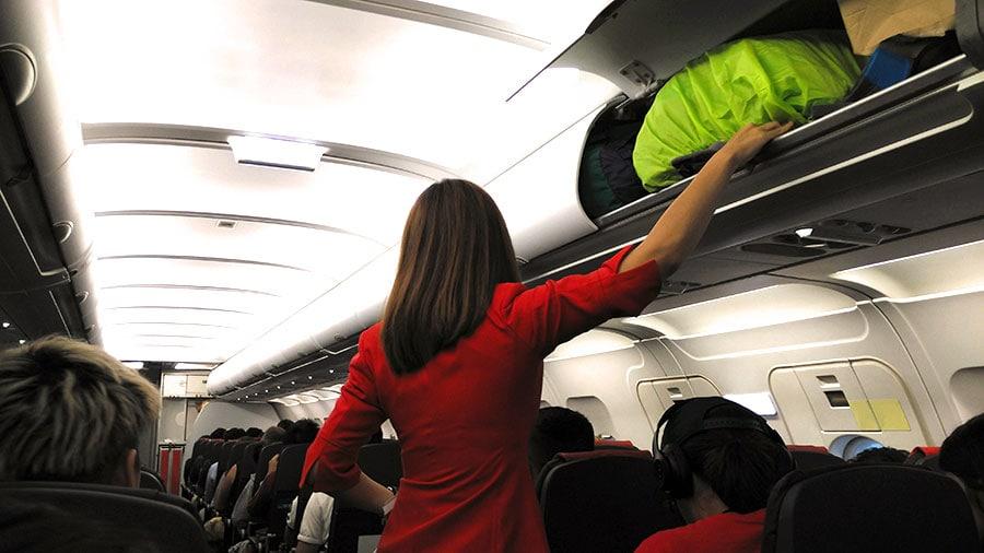 Requisitos de altura: Azafata colocando equipaje en el avión